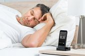 stock photo of early-man  - Mature Man Sleeping On Bed With Alarm On A Digital Cell Phone Display  - JPG