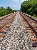 picture of trestle bridge  - Two sets of railroad tracks run parallel toward the horizon in rural Indiana - JPG
