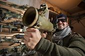 stock photo of beret  - Arms merchant in the beret and sunglasses with the jet grenade launcher on the weapon display background - JPG
