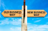 picture of arrow  - Wooden signpost with two opposite arrows over clear blue sky Old Business Way and New Business Way Business change conceptual image - JPG