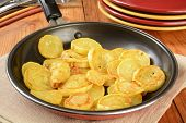 stock photo of sauteed  - Sauteed summer squash in a frying pan with serving plates in background - JPG