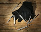 stock photo of pick-lock  - Lock picks with gloves on wooden table - JPG