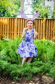 picture of bunny ears  - A young girl poses like a bunny rabbit outside in a garden wearing Easter bunny ears eating a fresh carrot during the spring season - JPG