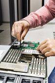 stock photo of chassis  - young man IT engineer repair server in the data center - JPG