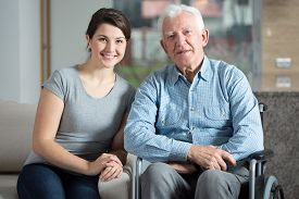 stock photo of wheelchair  - Young pretty female caretaker and elderly man on a wheelchair - JPG
