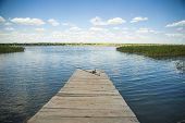 pic of rod  - Lonely fishing rod on old wooden pier on the lake - JPG