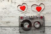 foto of magnetic tape  - Audio cassette with magnetic tape in shape of hearts on wooden background - JPG