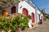 picture of windows doors  - Typical Greek house with white walls and red wooden doors and windows with red flowers in front and scooter standing on the street in background  - JPG