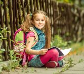 picture of schoolgirls  - Little pretty schoolgirl reading a book sitting on the street - JPG
