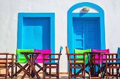 stock photo of greek-architecture  - Colorful Greek restaurant table and chairs in front of iconic blue wooden doors and white walls in Greece - JPG