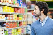 pic of supermarket  - Attractive man shopping in a supermarket - JPG