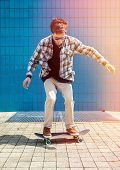 foto of skateboard  - Skateboarder jumping in city on skateboard at the background wall tiles - JPG