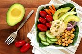 picture of lunch  - Healthy lunch bowl with avocado hummus and fresh vegetables overhead scene on wooden table - JPG