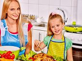 foto of pinafore  - Mother and daughter cooking chiken food at kitchen - JPG