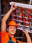 stock photo of suspenders  - Man in builder in uniform and hardhat installing suspended ceiling - JPG