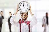 stock photo of suspenders  - Funny man wearing suspenders holding big clock - JPG