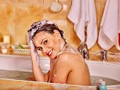 stock photo of bubble-bath  - Happy woman washing hair in bubble bath - JPG