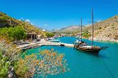 stock photo of greek-island  - Wooden yacht standing in cosy port on Greek island with clear blue water - JPG