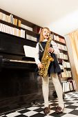 pic of saxophones  - Girl in school uniform dress plays on the alto saxophone standing near the piano indoors - JPG