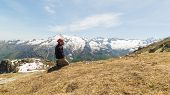 stock photo of kneeling  - Side view of adult hiker with sunglasses and beard kneeling on the mountain summit - JPG