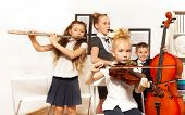 foto of cello  - School children playing musical instruments together during their concert in school - JPG