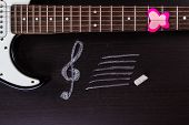 picture of clefs  - Electric guitar with treble clef on dark background - JPG