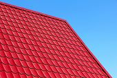 stock photo of red roof  - Red roof tiles taken closeup against of blue sky - JPG