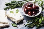 pic of kalamata olives  - Feta cheese with olives and green herbs on gray marble background - JPG