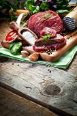 picture of meats  - Raw meat on wooden cutting board with herbs - JPG