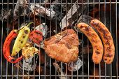 picture of grilled sausage  - Pork chop steak and vegetable with sausage on a flaming BBQ grill - JPG