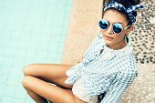 foto of beside  - Fashion photo of sexy beautiful Girl in plaid shirt and sunglasses relaxing beside a swimming pool - JPG