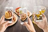pic of grilled sausage  - friends using smartphones to take photos of sausage and pork chop and beer - JPG