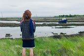 stock photo of marsh grass  - A young woman is walking in the marshes and is looking at a boat - JPG