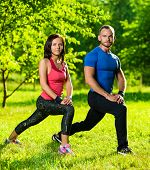 foto of stretch  - Man and woman doing stretching exercises at summer park - JPG