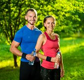 stock photo of cold drink  - Man and woman drinking water from bottle after fitness sport exercise - JPG