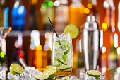stock photo of mojito  - Mojito cocktail drink on bar counter with blur bottles on background - JPG