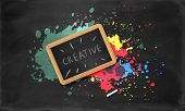 picture of decomposition  - Slate in wooden frame with the word creative on it and a piece of chalk on black background with colorful splatters - JPG