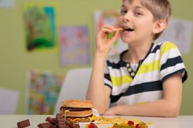 stock photo of obese children  - School child eating unhealthy snacks for lunch - JPG