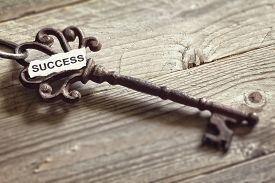 stock photo of skeleton key  - Antique key with word success written on paper resting on wooden surface concept for aspirations and success - JPG