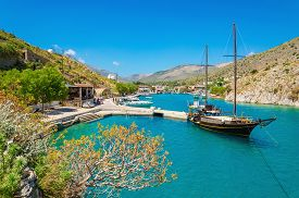 image of greek-island  - Wooden yacht standing in cosy port on Greek island with clear blue water - JPG