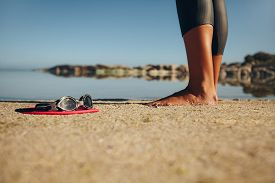 pic of wet feet  - Swim goggles on the sand with feet of a woman standing by - JPG