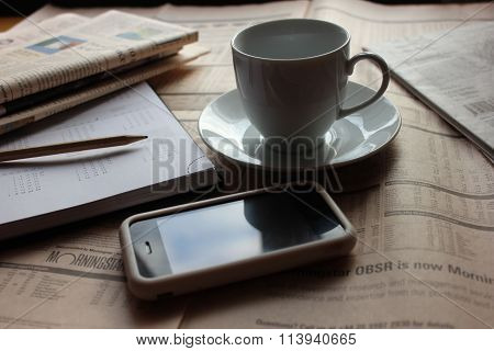 Stationery with newspapers, smartphone and cup of cofee