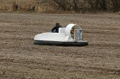 picture of hydrofoil  - a small hovercraft is driven across a farm field - JPG