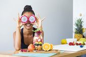 Woman smiling with a tropical fruit salad, being playful covering her eyes with dragon fruit poster
