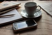 Постер, плакат: Stationery with newspapers smartphone and cup of cofee