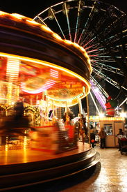 stock photo of ferris-wheel  - funfair at night with brightly lit big-wheel and carousel  - JPG