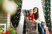 Young Beautiful Happy Mother With A Cute Little Baby Boy Sitting On A Wicker Chair In A Decorated Ro poster