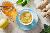 Lemon and ginger tea with honey. Cup of hot honey lemon tea with fresh ginger root. poster