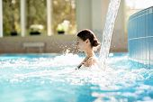 Serene girl enjoying stream of waterfall and its gentle splashes in swimming-pool at spa resort poster