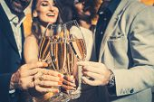 Men and women celebrating birthday or new years party while clinking glasses with sparkling wine poster